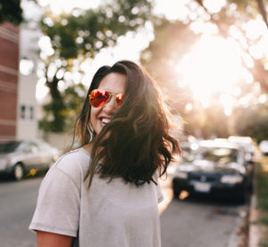 woman wearing sunglasses smiling on the street
