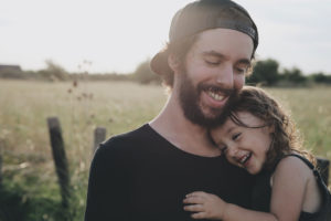 smiling father holding his young daughter