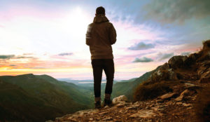 man standing on mountain peak looking out at sunset