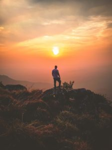 man standing on rocks on a mountain at sunset